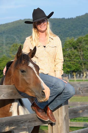 Cowgirl sitting on fence in causual western style clothes and cowboy boots and hat.