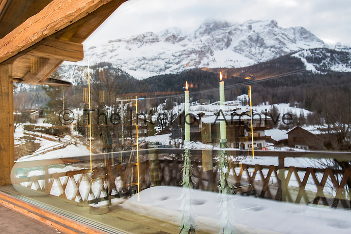 Reflection of snow covered chalets and the Italian Alps in the chalet's living room window