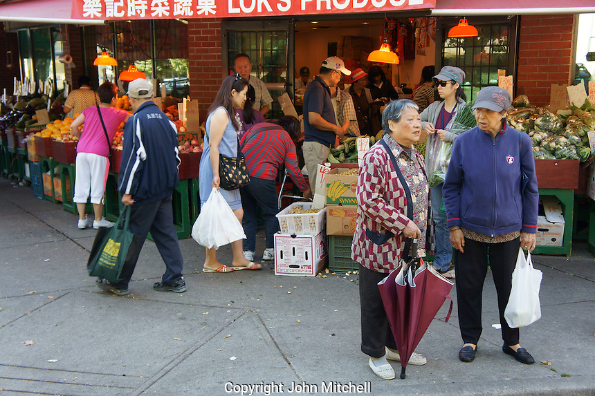 Two elderly Chinese women outside a produce store, Chinatown, Vancouver, British Columbia, Canada