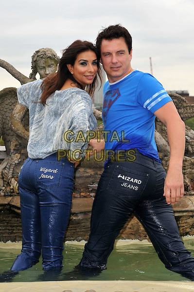 Shobna Gulati & John Barrowman.Wizard Jeans Rear Of The Year Award 2012, Dorchester Hotel, London, England..June 27th, 2012.half length sweater jumper jeans denim wet water fountain 3/4 back behind blue grey gray white knitted looking over shoulder top t-shirt .CAP/BF.©Bob Fidgeon/Capital Pictures.