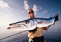 Maldives, November 2008. Fisherman in his 40s holding a very large Barracuda caught on a jig in the Indian Ocean waters. Horizontal