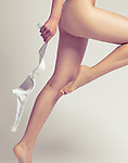 Young naked woman taking off her bra, artistic sensual closeup of legs
