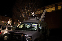 People sit in a news van outside the site of the GOP debate at St. Anselm College in Manchester, New Hampshire, on Jan. 7, 2012.
