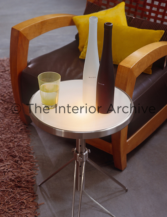 Coloured bottles on a round table beside a designer armchair in the living room