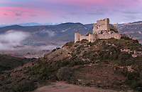"Aguilar Castle, Chateau d'Aguilar, Cathar Castle, Tuchan, Corbieres, Aude, France. The castle consists of an inner keep built in the 12th century, surrounded by an outer pentagonal fortification from the 13th century with semi-circular guard towers, and is one of the ""Five Sons of Carcassonne"" or ""cinq fils de Carcassonne"". It is a listed monument historique. View from distance showing hilltop location. Picture by Manuel Cohen"