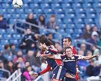New England Revolution forward Juan Toja (7), FC Dallas midfielder Andrew Jacobson (4), and New England Revolution substitute defender Kelyn Rowe (11) battle for head ball. .  In a Major League Soccer (MLS) match, FC Dallas (red) defeated the New England Revolution (blue), 1-0, at Gillette Stadium on March 30, 2013.