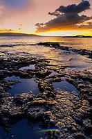 Sunset along a rocky shoreline on Maui.