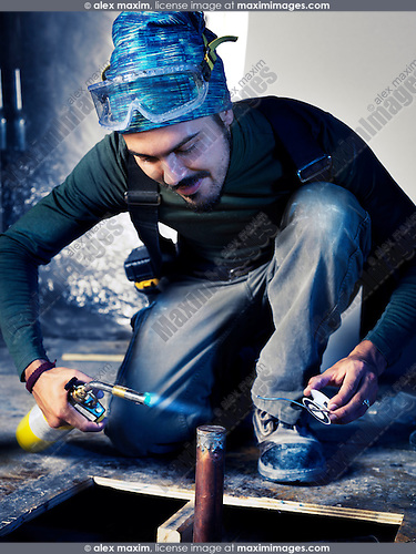 Portrait of man contractor worker with a blow torch capping a pipe doing plumbing