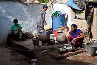 Sadma Khan's relatives wash crockery in the common washing area of her mother's extended family's  shared housing compound in a slum area of Tonk, Rajasthan, India, on 19th June 2012. Sadma, now 19, was married at 17 years old to Waseem Khan, also underaged at the time of their wedding. The couple have an 18 month old baby and Sadma is now 3 months pregnant with her 2nd child and plans to use contraceptives after this pregnancy. She lives with her mother since Waseem works in another district and she can't take care of her children on her own. Photo by Suzanne Lee for Save The Children UK