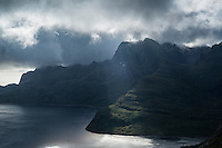 Sunlight pierces through clouds on Solbjørnvatnet, Moskenesoy, Lofoten Islands, Norway