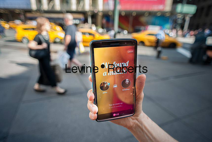 A traveler looks at her smartphone with the Bandwagon app at the taxi line in front of Pennsylvania Station in New York on Wednesday, October 19, 2016. Bandwagon, partnering with the 34th Street Partnership BID, started providing taxisharing services at Penn Station. This enables commuters to be hooked up with another rider, splitting the fare using technology built into the taxi meter.  (© Richard B. Levine)