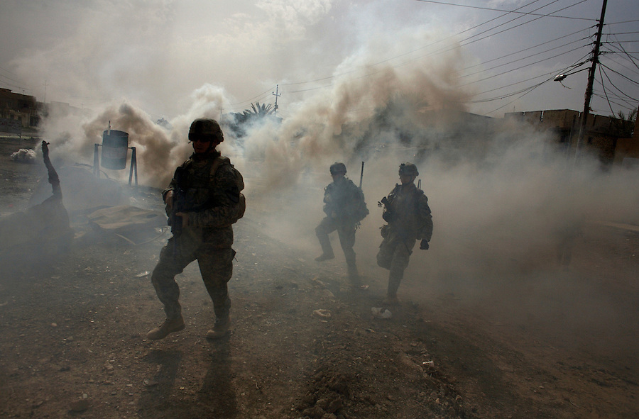 Soldiers from 5-20 Infantry 3HBCT 2nd Infantry Division run through smoke meant to shield them sniper fire as they patrol in the Diyala provincial capital, Baqubah, on Friday June 1, 2007.
