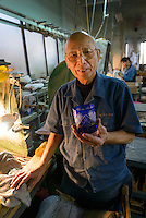 Edokiriko artisan Ryuzo Mita holds a half-finished glass. Shimizu Glass, Tokyo, Japan, January 14, 2015. Edokiriko is a style of cut glass that dates back to 1834 and is similar to British cut glass. It makes use coloured glass and highly-intricate Japanese motifs.