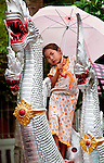 A girl finds a good viewing platform of the Lao New Year (Pi Mai ) parade in Luang Prabang on the back of the fabled Naga, water serpent.