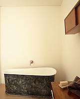 A free-standing contemporary interpretation of an old-fashioned bath tub has been installed in this small bathroom