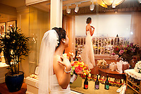 A bride poses at the Claremont Hotel while looking at a photo of a bride in Berkeley.