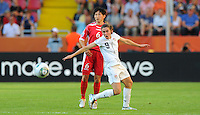 Heather O'Reilly (r) of Team USA and Paek Sol Hui of Team North Korea during the FIFA Women's World Cup at the FIFA Stadium in Dresden, Germany on June 28th, 2011.