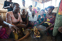 Africa, DRC, Democratic Republic of the Congo, South Kivu, Kamanyola. Women for Women project. WFW Kamanyola co-op and lifeskills training. Women learning restaurant skills cook a chicken.