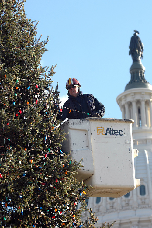 Richard Prince, Architect of the Capitol, takes lights off of the Capitol Christmas tree, on the west front.