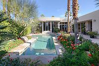 lush landscaping surrounds swinning pool at large modern residence