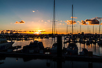 Christmas Eve sunset, with sunburst, at the San Leandro Marina  with sailboat masts in silhoutte.