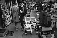 Twins sleep in a pram in London's Camden Town market.