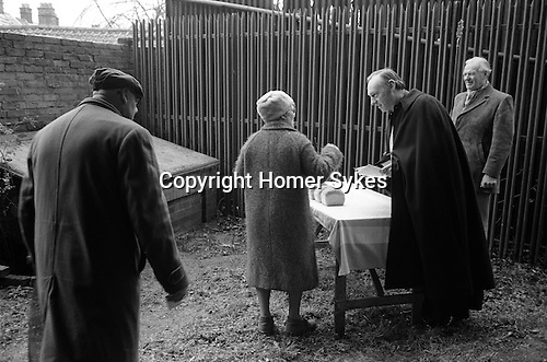 Carlow's Charity Woodbridge Suffolk.1975<br /> The Revd Canon Rowlands, accompanied by Churchwarden Mr George Thacker, distributes loafs of bread to those pensioners who qualify from a table set up in a back yard of the Bull Hotel. This is the site of Carlow's Tomb.<br /> George Carlow, who died in 1738, was a member of a religious sect called 'Separate Congregation', one of whose beliefs was that Saturday should be kept as the Sabbath. Before he died, Carlow had a vault built in the garden of his house, on which was inscribed :<br /> <br /> Weep for me dear friend no more for I am gone a little before.But by a lite of pity prepare yourself to follow me. Good friends for Jesus sake forbear To move the dust entombed here.<br /> Blessed be he that spares these stones. Cursed be he that moves my bones. Twenty shillings worth of bread to be given on this stone to the poor of the town on the second of February forever.<br /> <br /> This inscription records the directive in his will that the rent from his premises (now covered by the new annex of the Bull Hotel) should go towards the upkeep of his tomb, and that every year on Candlemas day (2 February) the churchwardens from St Mary's should purchase twenty shillings worth of twopenny loaves from the two poorest bakers in the town, and give them to the poor of the parish. Moreover, this was to 'go on for ever'. At present, since loaves cost more than two pence, only twelve loaves are purchased and distributed by the rector of St Mary's  the help of the verger and two churchwardens. Sherry is then taken in Carlow's room in the Bull Hotel by all those taking part.