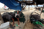 A Palestinian fisherman rests at Gaza Seaport in Gaza City September 30, 2012. Israel confines fishermen within a three-mile fishing zone in the Mediterranean Sea off the coast of Gaza, Palestinian fishermen syndicate said. A Palestinian man died on Saturday after he was shot by Israeli troops while fishing on the beach in the Gaza Strip, said Hamas officials, while an Israeli military spokeswoman said the man was shot when he approached the border fence. Photo by Ashraf Amra