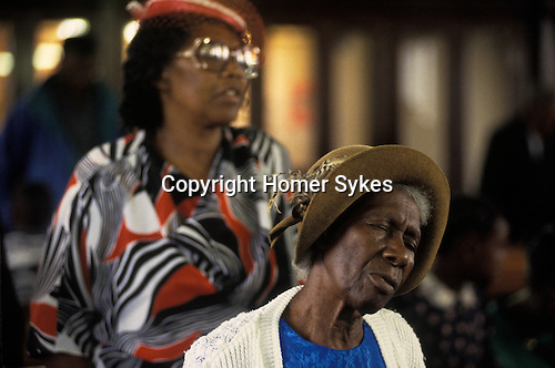 Women members of the Church of God of Prophecy West London during a sunday church service.  from A STORM IS PASSING OVER a Look at Black Churches in Britain. Published by Thames and Hudson isbn 0 500 27826 1
