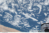 In Earth Orbit - May 15, 2009 -- Low-level winds rushing over the Cape Verde Islands off the coast of northwestern Africa created cloud vortex streets which share this scene with the top of the Hubble Space Telescope locked down in the cargo bay of the Earth-orbiting Space Shuttle Atlantis..Credit: NASA via CNP