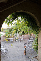 View through an archway onto the stone tiled terrace set for dinner with a number of tables for the guests