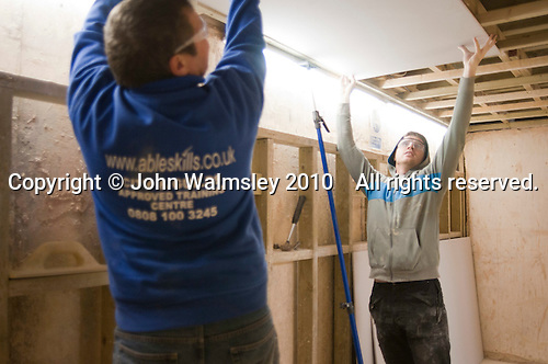 Plastering student fixes a sheet of plasterboard to the ceiling rafters with help from an instructor, Able Skills, Dartford, Kent.