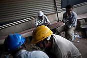 Indian daily wage labourers take a break at the construction site of the Adani Power plant of 4620 MW capacity in Mundra port industrial city of Gujarat, India. Indian power companies have handed out dozens of major contracts to Chinese firms since 2008. Adani Power Ltd have built elaborate Chinatowns to accommodate Chinese workers, complete with Chinese chefs, ping pong tables and Chinese television. Chinese companies now supply equipment for about 25% of the 80,000 megawatts in new capacity.
