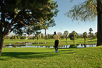 Golfer hitting in Fairway over water to Green