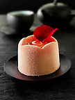 modern designed white chocolate cake with a sponge case and strawberry filling, covered with pink white chocolate powder in a  Traditionl black Japanese tea setting