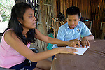 Eleven-year old Juan Lopez reads his homework - in Braille - with the help of his sister Griselda at their home in Zipolite, a town in Oaxaca, Mexico. Both are blind. Juan refuses to be sidelined by his disability, however. He rides his bike, for example, with his sister's help. She perches on the back and signals him which way to steer by pinching his shoulder. If she pinches his right shoulder, for example, he goes right. The harder the pinch, the sharper the turn.