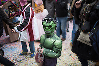 A young masked participant walks with a bag of red confetti in Fasnacht's Carnival of Children on the second day of the festival in the old town of Basel, Switzerland. Feb. 24, 2015.