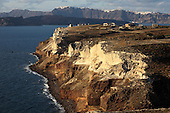 Cliffs of Cape Apronisi exposing cycle 1 eruption products covered with the lighter tuff deposits from the Minoan Eruption of Santorini Volcano, Greece. Kameni Islands and the main Caldera wall are in the background.