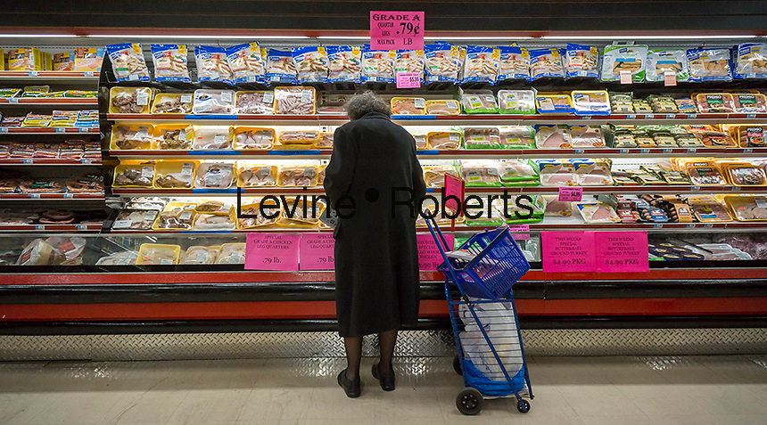 "A senior citizen shops for chicken in the meat department of a supermarket in New York on ""Senior Tuesday"", March 8, 2016. (© Richard B. Levine)"