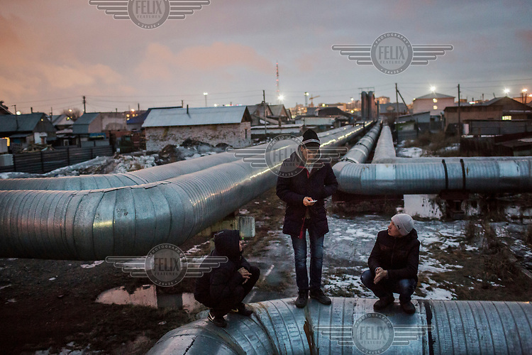 A group of teenagers hang out a heating pipe, part of a network which supply heat to the right bank district.