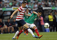 MEXICO CITY, MEXICO - AUGUST 15, 2012:  Geoff Cameron (20) of the USA MNT kicks the ball away from Angel Reyna (10) of  Mexico during an international friendly match at Azteca Stadium, in Mexico City, Mexico on August 15. USA won 1-0.