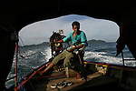 A driver operates a traditional Thai longtail boat in the tropical islands near Koh Ngai (also known as Koh Hai) in the Trang Archipelago near Trang on the West Coast of Thailand.