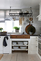 In the kitchen contemporary cupboards and vintage elements such as the antique butcher's block and metal rack harmonise effortlessly