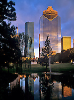 Stock photo of late afternoon view of downtown Houston,Texas featuring the Wells Fargo Plaza on left and Heritage Plaza on right reflected in the pond at Sam Houston Park.