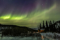 Aurora borealis swirls over Windy Gap cabin in the White Mountains National recreation area in interior Alaska.