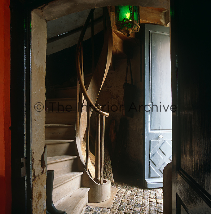 A simple wooden staircase spirals up from a narrow cobbled hallway leading off the kitchen at the back of the property