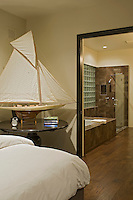 Model sailboat is seen in bedroom looking towards bathroom entry