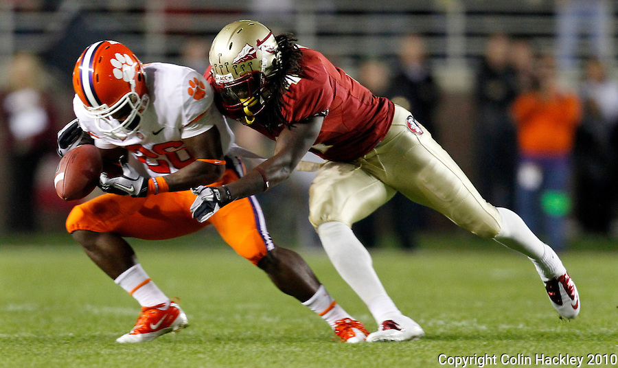 TALLAHASSEE, FL 11/13/10-FSU-CLEMSON FB10 CH-Florida State's Terrance Parks, right, knocks the ball loose from Clemson's Marquan Jones as FSU's Greg Reid, left, closes during first half action Saturday at Doak Campbell Stadium in Tallahassee. .COLIN HACKLEY PHOTO