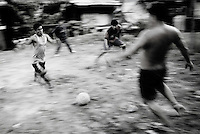 Iquitos, Peru, Jan. 11, 2007 - Two boys vie for the ball during a makeshift soccer match on a dry patch of ground in the neighborhood of Bélen, a small poverty-stricken area built along the flats of the Amazon River. It is comprised of homes built on stilts or of floating balsa wood. During the wet season the river rises several meters causing those on stilts upstairs and all other to float. Children pass time by swimming in the river and looking for dry patches of land, as here, to play soccer.