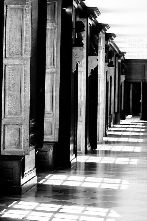Interior view of long corridor with sunlight shining in through tall windows onto ornate tiled floor